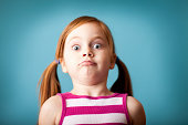 Color photo of a young girl with wide eyes and a crazy look of surprise.