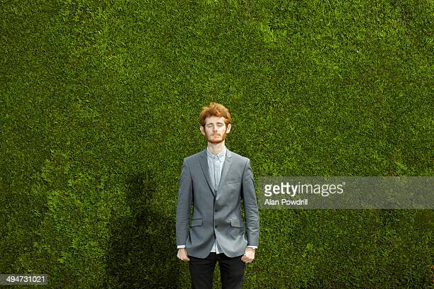 Red haired young man against huge green hedge