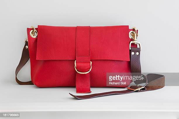 A red handbag on a white shelf