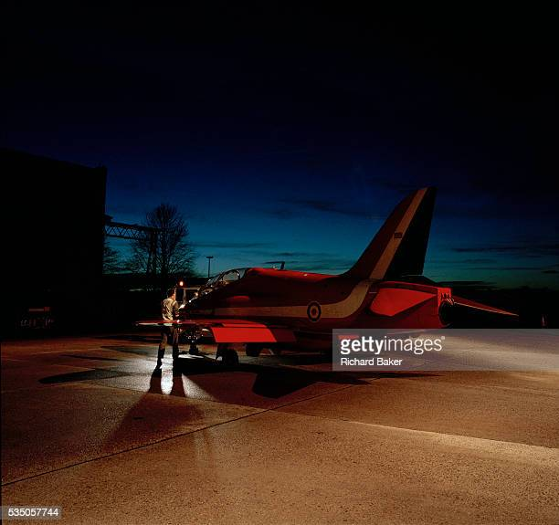 A red Hawk jet aircraft belonging to the elite 'Red Arrows' Britain's prestigious Royal Air Force aerobatic team is parked outside a nearby hangar on...