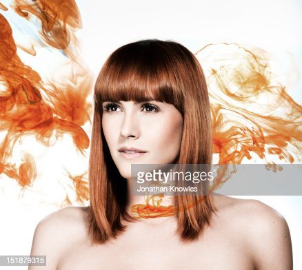 Red head female surrounded by orange liquid : Stock Photo