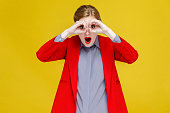 Red head woman in red suit looking in binoculars far far away. Studio shot, isolated on yellow background