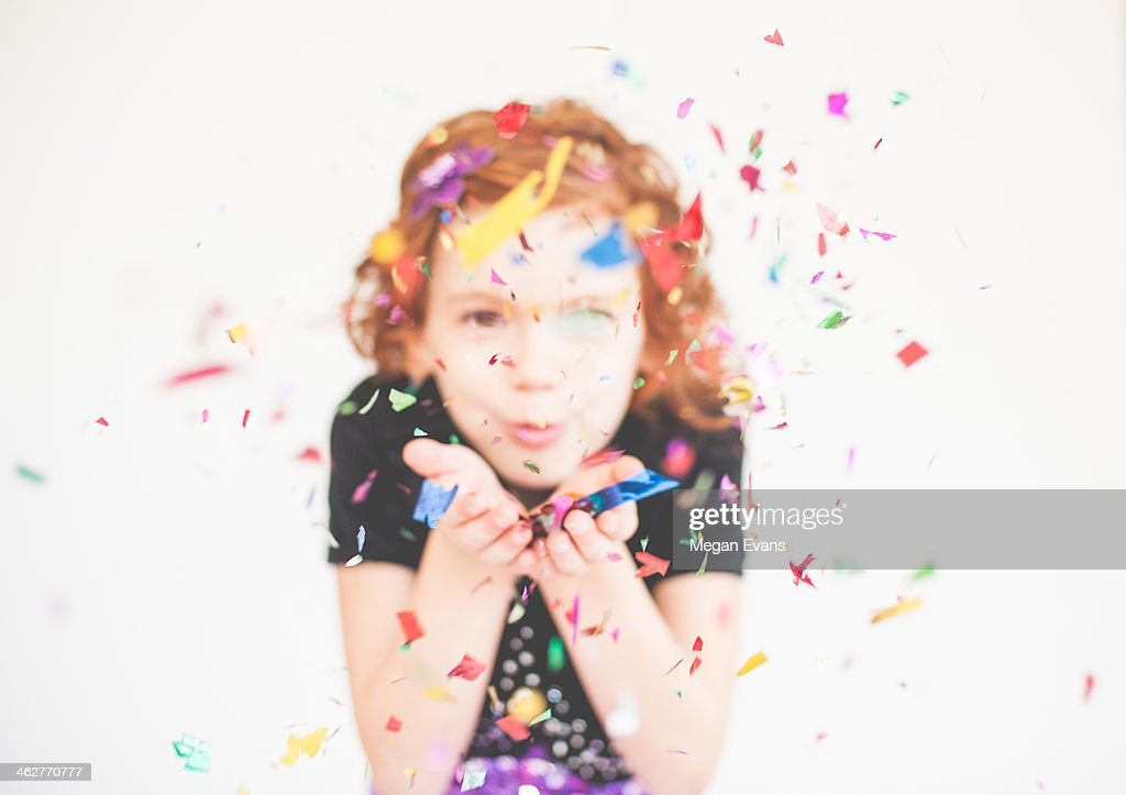 Red headed girl blowing confetti : Stock Photo