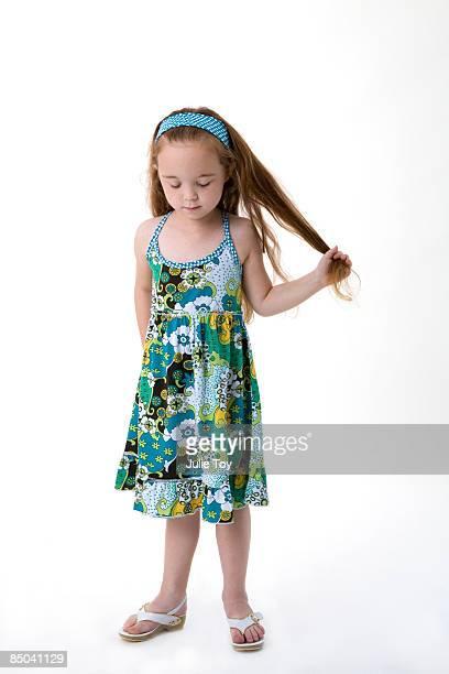 Red headed little girl pulling her hair