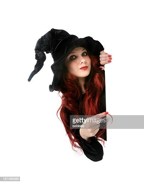 A red headed witch pointing to something in the distance