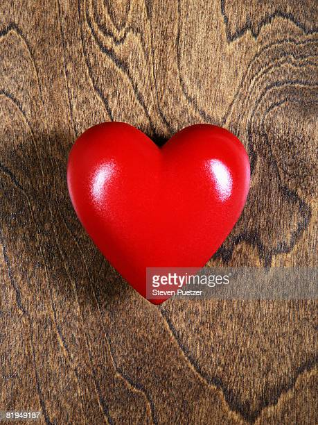 Red heart against wood background