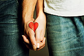 Red heart drawing on hands of couple