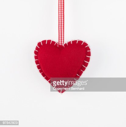 red heart hanging by checkered red ribbon