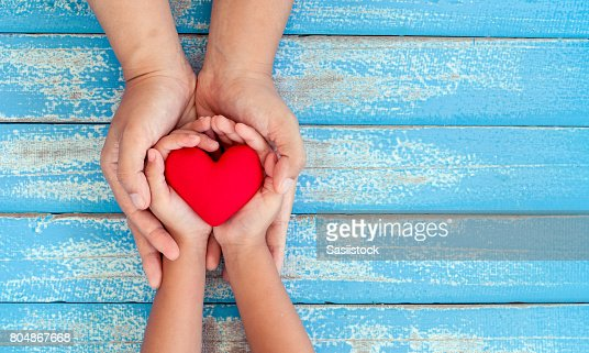 Red heart in child kid and mother hands on old blue wooden table : Stock Photo