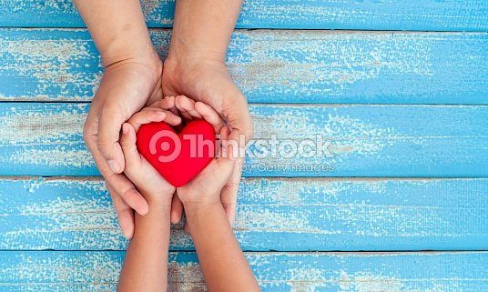 Red heart in child kid and mother hands on old blue wooden table : Foto stock