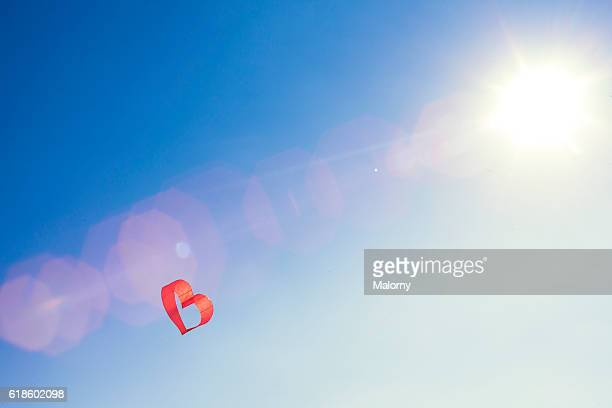 Red heart kite or balloon against blue sky. Love is in the air.