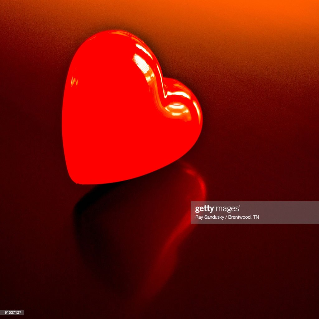 Red Heart on Reflective Surface with a Red Tint : Stock Photo