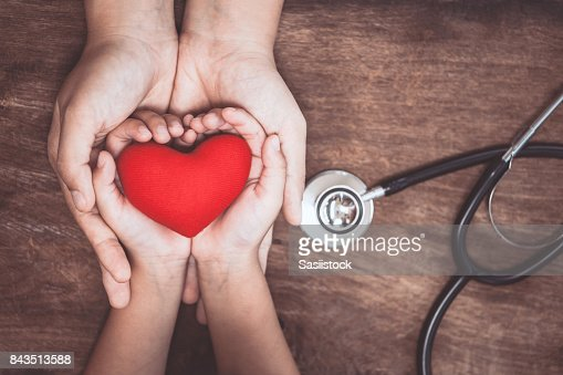 Red heart on woman and child hands and with doctor's stethoscope on wooden background : Stock Photo