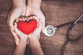 Red heart on woman and child hands and with doctor's stethoscope on wooden background. Healthcare medical  concept