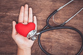 Red heart on woman's hand with doctor's stethoscope on wooden background. Healthcare medical  concept