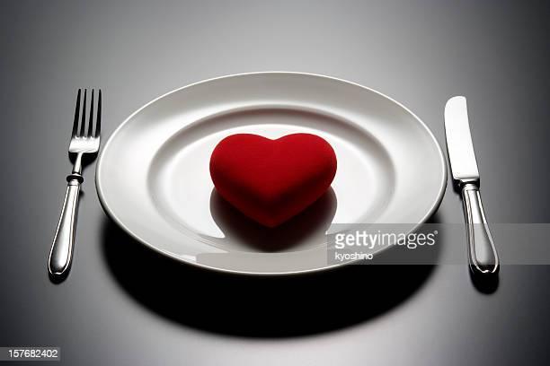 Rosso a forma di cuore con piatto su nero scrivania