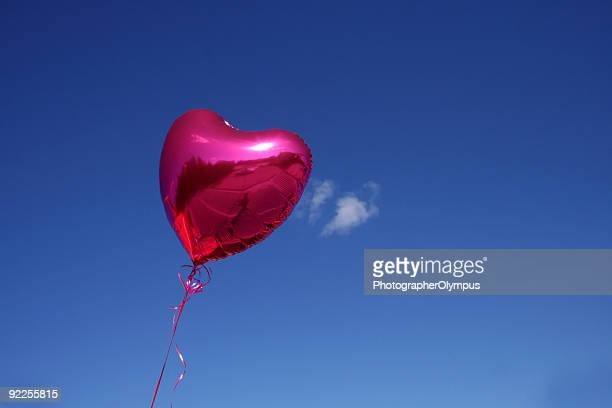 Red heart shaped balloon against the blue sky