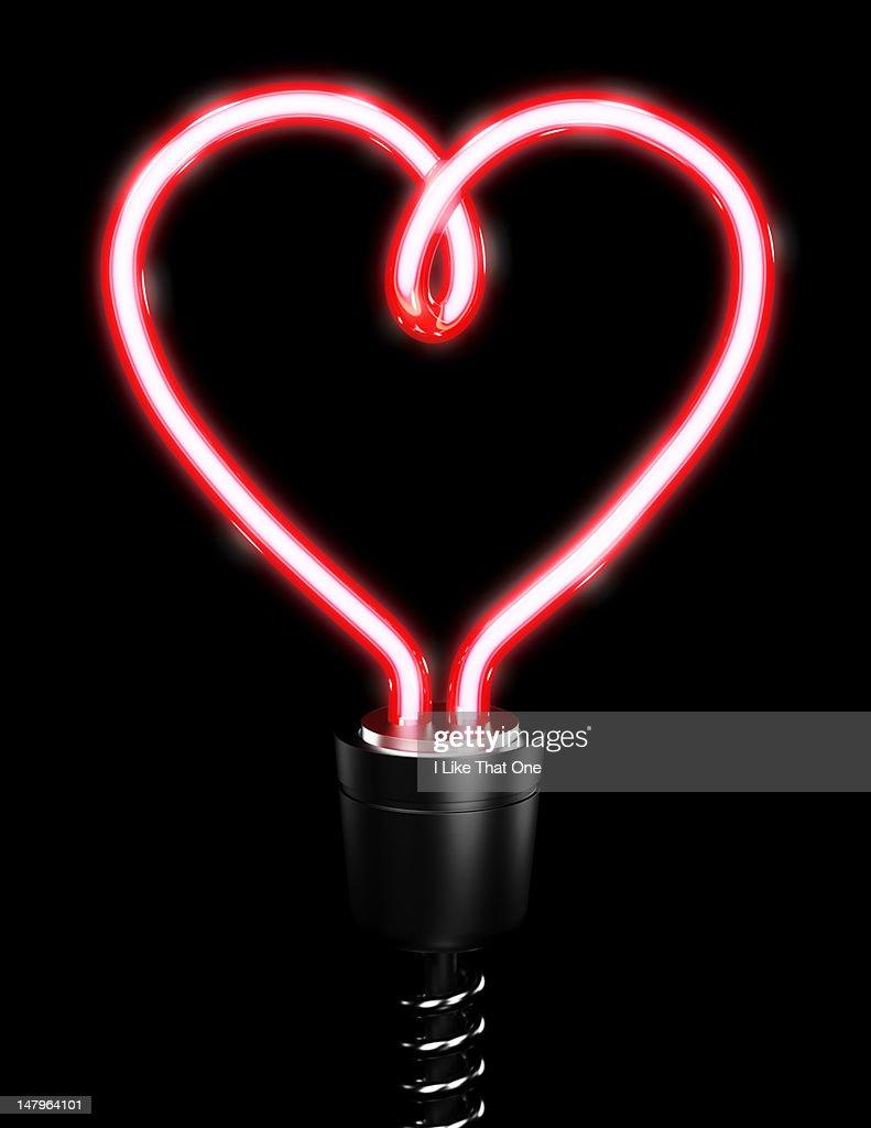 Red heart shaped energy saving lightbulb : Stock Photo