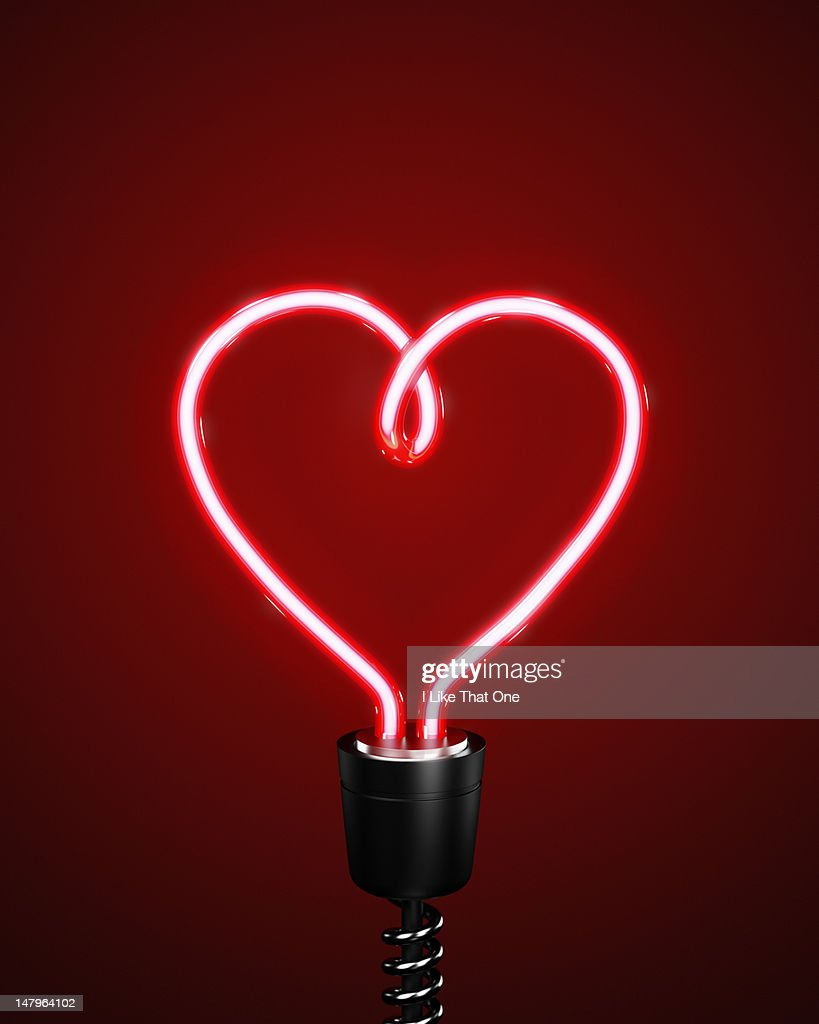 Red heart shaped energy saving lightbulb : Stock Photo