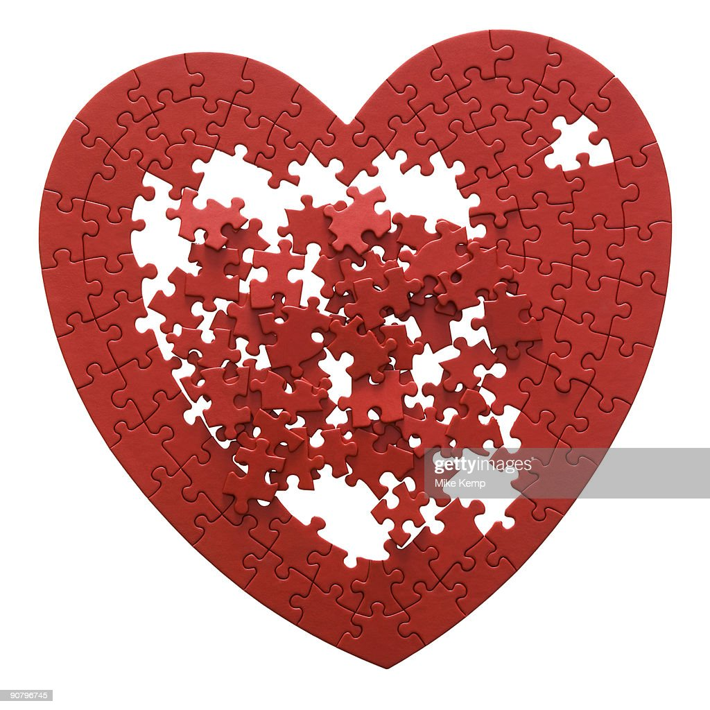 red heart shaped jigsaw puzzle on a white background : Stock Photo