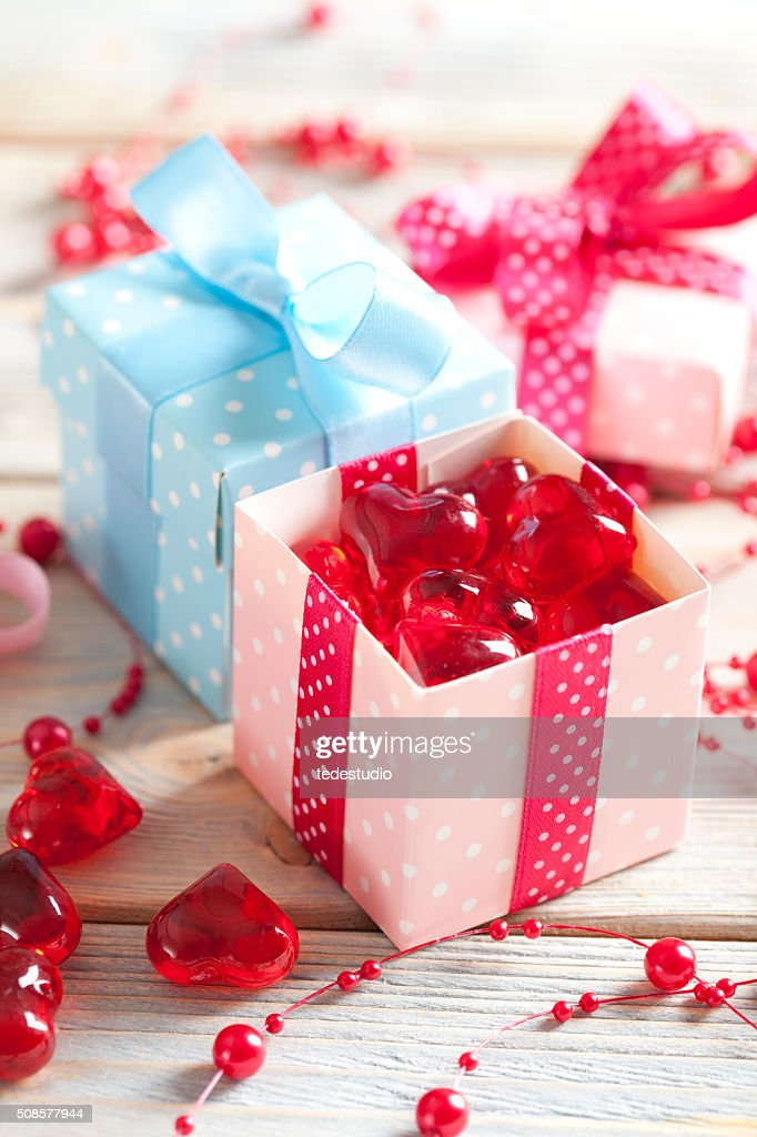 Red hearts and colored gift boxes on wooden background : Bildbanksbilder