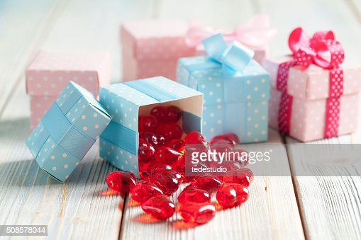 Red hearts and colored gift boxes on wooden background : Stock Photo