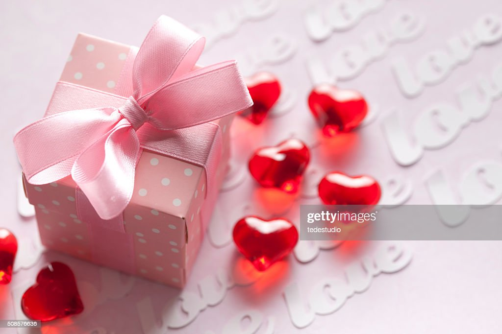 Red hearts and gift box on pink background : Bildbanksbilder