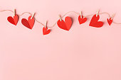 Beautiful valentines day paper hearts hanging on rope on pink background. View from above. Valentines Day Concept.