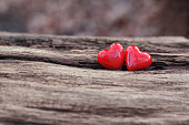 2 shiny red ceramic hearts on weathered wooden background