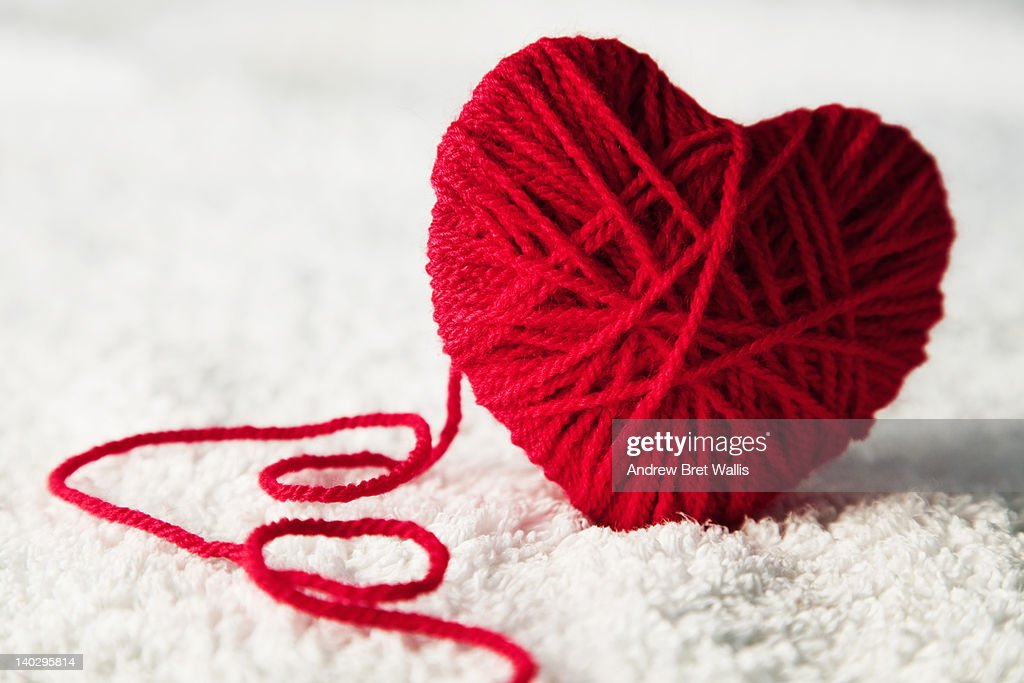Red heart-shaped wool ball unraveling : Stock Photo