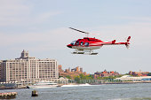 Red helicopter about to land above water