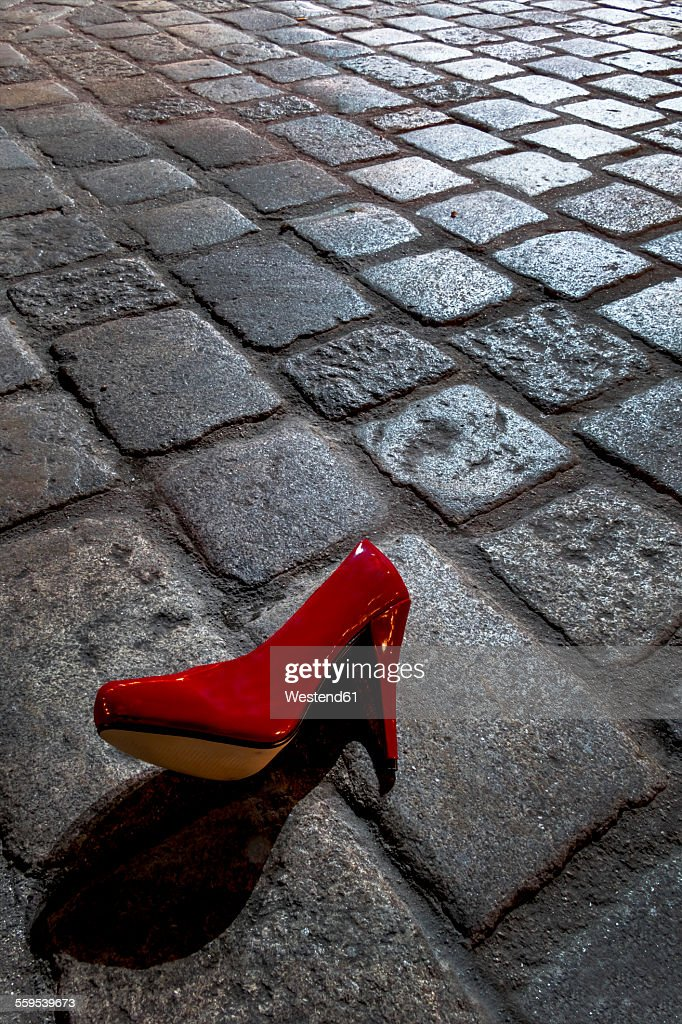 Red high heel lying on cobblestone pavement at night