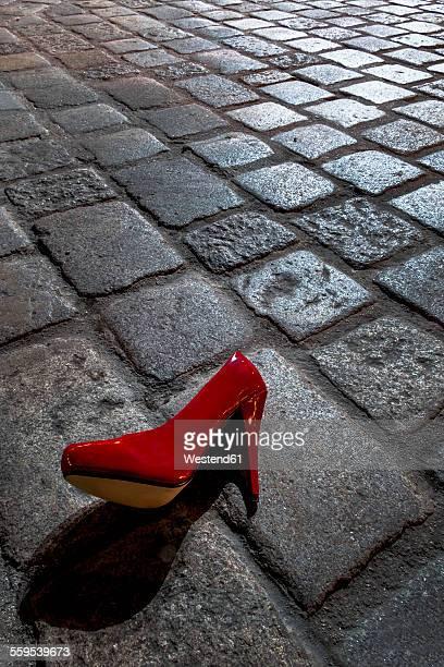 Red high heel lying on cobblestone pavement at night