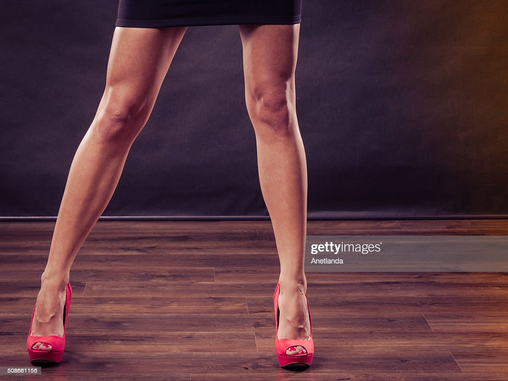 Red high heels spiked shoes on sexy female legs : Stock Photo