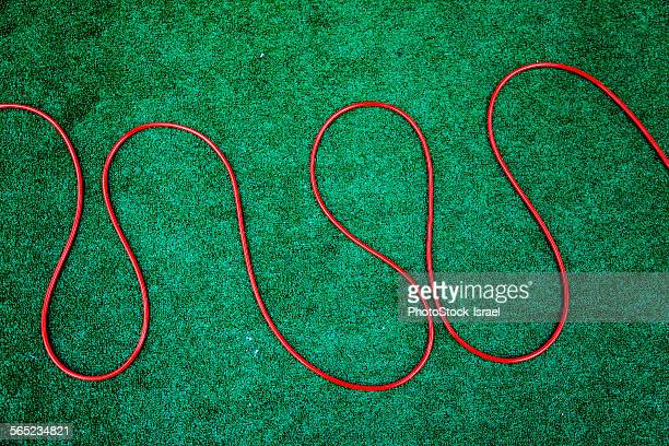Red hosepipe on green grass