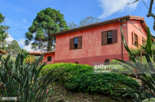 Red house surrounded by landscaping on day of clear sky and sun horizontally