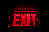 A red Illuminated exit sign on black