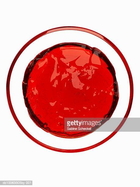 Red jelly in glass bowl on white background, overhead view