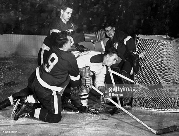 Red Kelly and teammate Gordie Howe of the Detroit Red Wings sandwich Maurice Richard of the Montreal Canadiens before he can score on goalie Terry...