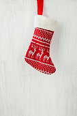 Red Knitted Christmas Stocking Hanging on White Wood Barn Board Fire Place. Scandinavian Ornaments. Festive Bright Cozy Atmosphere. Copy Space