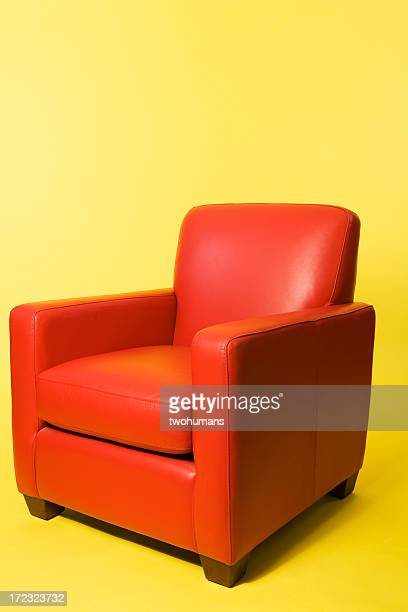 Red leather arm chair on a yellow background
