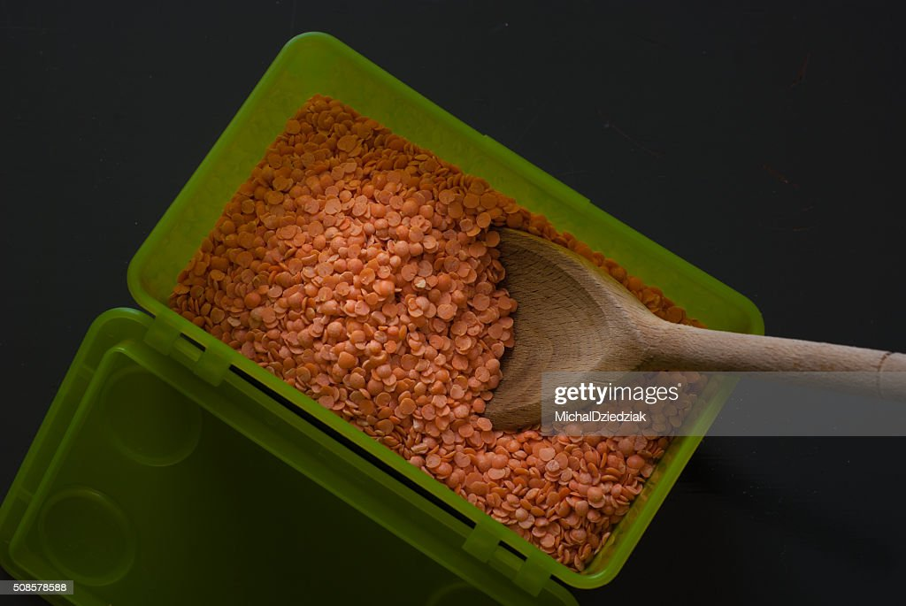 red lentil in green plastic box on dark wooden table : Stock Photo