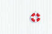 red lifebuoy on a old grunge wooden plank wall, summer concept, background