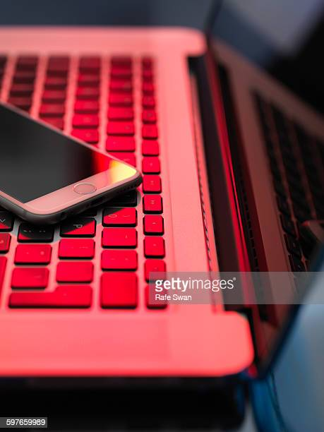 Red light on laptop and mobile phone illustrating danger from hackers
