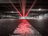 Low-Angle, Desaturated Light Trail Photo of Red Car Lights Moving Forward in a Parking Garage