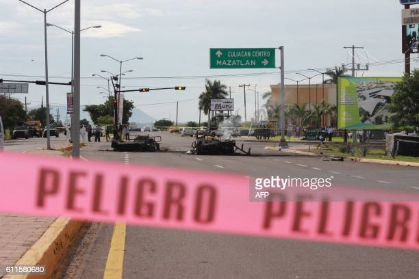 TOPSHOT A red line prevents the access to burned cars part of a military convoy which was ambushed by gunmen in Culiacan Sinaloa Mexico on September...
