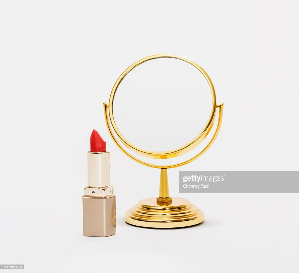 Red lipstick and gold beauty mirror