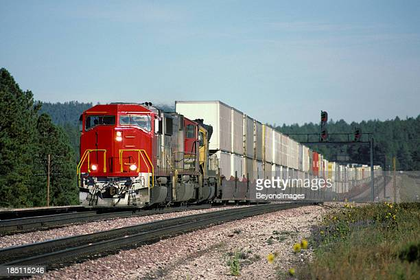 Red locomotive and double stack freight train