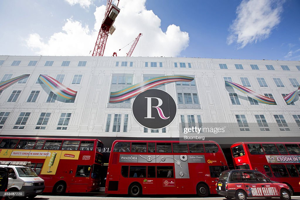 Red London buses pass hoardings outside the W5 commercial and retail construction complex, under development inside commercial real estate buildings that form part of the Pollen Estate, on Regent Street in London, U.K., on Monday, Aug. 11, 2014. Norway's sovereign wealth fund, Norges Bank Investment Management, the world's largest, bought a stake in the Pollen Estate in London's Mayfair district for 343 million pounds ($576 million), expanding its property holdings in the U.K. capital. Photographer: Jason Alden/Bloomberg via Getty Images