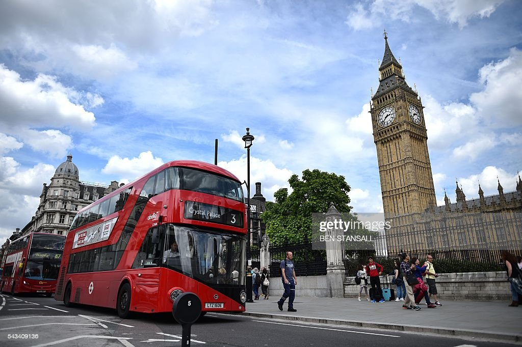 Red London buses travel past the Elizabeth Tower (C), which houses the 'Big Ben' bell in the Palace of Westminster in central London on June 28, 2016. EU leaders attempted to rescue the European project and Prime Minister David Cameron sought to calm fears over Britain's vote to leave the bloc as ratings agencies downgraded the country. Britain has been pitched into uncertainty by the June 23 referendum result, with Cameron announcing his resignation, the economy facing a string of shocks and Scotland making a fresh threat to break away. / AFP / BEN
